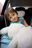 Adorable baby boy in safety car seat, holding teddy rabbit Royalty Free Stock Photography