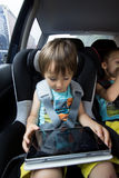 Adorable baby boy in safety car seat, playing on tablet Royalty Free Stock Image