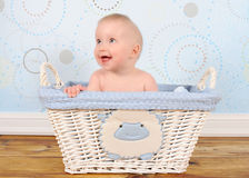 Adorable baby boy sitting in blue wicker basket Stock Photo