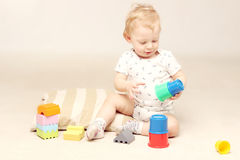 Adorable baby boy sitting on the floor and playing with his toys. Studio shot of adorable baby boy sitting on the floor and playing with some toys stock image
