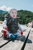 Adorable baby boy sitting outdoors on a wood deck Royalty Free Stock Photo