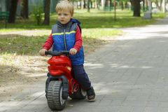 Adorable Baby Boy Sitting On A toy Motorcycle in the park. copy space.  royalty free stock image