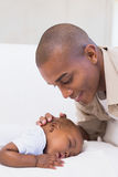 Adorable baby boy sleeping while being watched by father Stock Photos