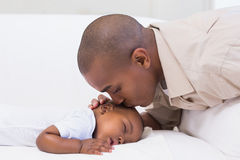 Adorable baby boy sleeping while being watched by father royalty free stock images