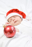 Adorable baby boy sleeping in christmas hat stock image