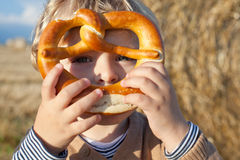Adorable baby boy with soft pretzel in evening sun Stock Images