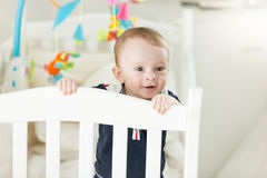 Adorable baby boy standing in bed and leaning on fence. Portrait of adorable baby boy standing in bed and leaning on fence Stock Photos