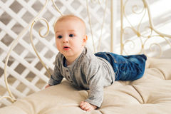 Adorable baby boy in sunny bedroom. Newborn child relaxing. Nursery for young children.Family morning at home. Little Royalty Free Stock Photo