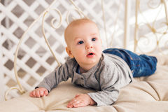 Adorable baby boy in sunny bedroom. Newborn child relaxing. Nursery for young children.Family morning at home. Little Stock Image