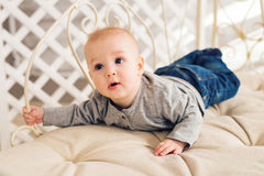 Adorable baby boy in sunny bedroom. Newborn child relaxing. Nursery for young children.Family morning at home. Little Stock Images