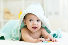 Adorable baby boy under a hooded towel after stock photography