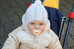 Adorable baby boy in warm clothes on tricycle Stock Images