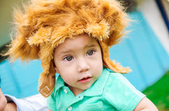 Adorable baby boy wearing turquoise t-shirt and big furry brown hat Royalty Free Stock Photo