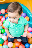 Adorable baby boy wearing turquoise t-shirt playing with colored plastic balls shot from above angle Royalty Free Stock Photography
