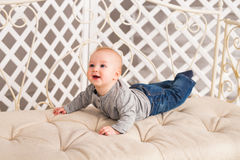 Adorable baby boy in white sunny bedroom. Newborn child. Nursery for young children. Family morning at home. Stock Photos