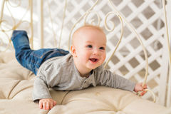Adorable baby boy in white sunny bedroom. Newborn child. Nursery for young children. Family morning at home. Royalty Free Stock Images