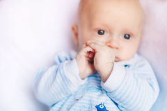 Adorable baby boy in white sunny bedroom Stock Image