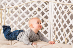 Adorable baby boy in white sunny bedroom. Newborn child relaxing. Family morning at home. Royalty Free Stock Photos
