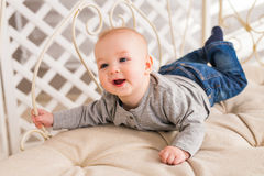 Adorable baby boy in white sunny bedroom. Newborn child relaxing. Family morning at home. Stock Photo