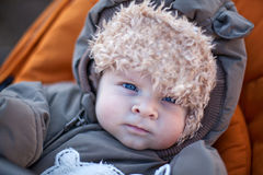 Adorable baby boy in winter clothes. Sleeping in orange stroller outdoor Royalty Free Stock Photo