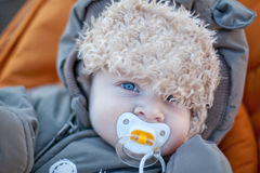 Adorable baby boy in winter clothes. Sleeping in orange stroller outdoor Royalty Free Stock Images