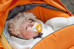 Adorable baby boy in winter clothes. Cute little baby boy in winter clothes sleeping in orange stroller outdoor Stock Photos