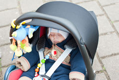Adorable baby boy in winter clothes. Sleeping in child car seat Stock Images