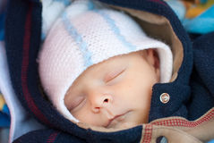 Adorable baby boy in winter clothes sleeping. In orange stroller outdoor Royalty Free Stock Photography