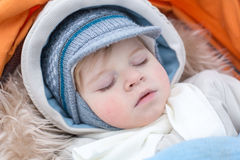Adorable baby boy in winter clothes sleeping in stroller Stock Photos