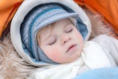 Adorable baby boy in winter clothes sleeping in stroller. Adorable baby boy in winter clothes sleeping in orange stroller outdoor Stock Photos