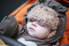 Adorable baby boy in winter clothes sleeping in stroller. Adorable baby boy in winter clothes sleeping in orange stroller outdoor Royalty Free Stock Image