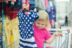 Adorable baby on cart choose clothes Royalty Free Stock Photo
