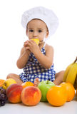 Adorable baby chef eating fruits Stock Photos