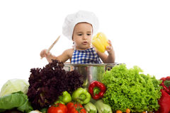 Adorable baby chef prepare healthy vegetables food Stock Image