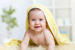 Adorable baby child under bathing towel indoor. Adorable happy baby child under bathing towel indoor stock photography