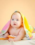 Adorable baby in colorful towel after bath royalty free stock images