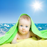 Adorable baby in colorful towel on sea beach Stock Images