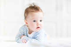 Adorable baby doing her tummy time in a white nursery Royalty Free Stock Photo