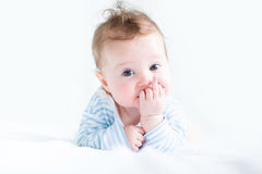 Adorable baby doing her tummy time in a white nursery royalty free stock image