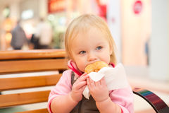Adorable baby eat donut in mall. Adorable baby eat donut holding it with napkin in mall Royalty Free Stock Photos
