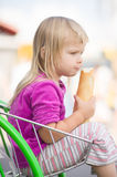 Adorable baby eat long bread, sit in cart Stock Photo