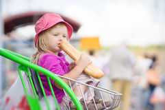 Adorable baby eat long bread, sit in cart Royalty Free Stock Image