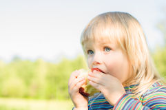 Adorable baby eat red apple in park Stock Photo