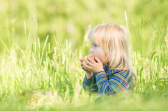 Adorable baby eat red apple sitting on grass Stock Photos
