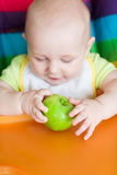 Adorable baby eating apple in high chair Royalty Free Stock Photo
