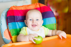 Adorable baby eating apple in high chair Royalty Free Stock Image