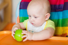 Adorable baby eating apple in high chair Stock Photos