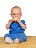 Adorable baby eating a bun. Adorable small baby sitting on the carpet eating a bun with a look of contentment against a white background royalty free stock images