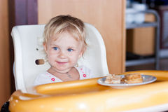 Adorable baby eating cake in a chair Stock Photography