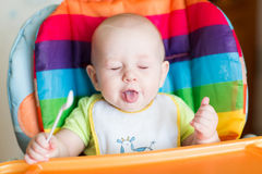 Adorable baby eating in high chair Royalty Free Stock Photography